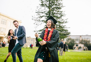 Student at graduation popping a bottle of champagne